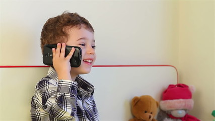 Little boy talking on smartphone at home