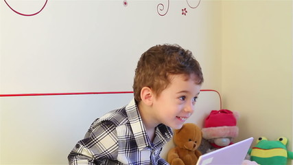 Surprised little boy watching laptop