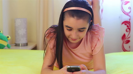 Teenager girl playing on smartphone
