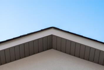 Top of house roof edge on clear sky.