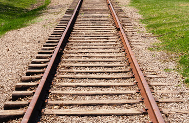 Receding train tracks near grass.
