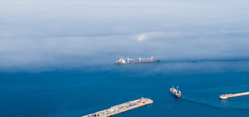 Cargo ships in fog near harbor entrance.