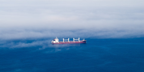 Large cargo ship in partial fog.