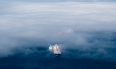 Cargo ships emerging from fog.