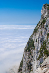 Gibraltar cliff face above clouds on sky.