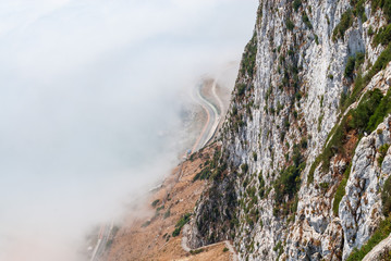 Gibraltar cliff face above fog.