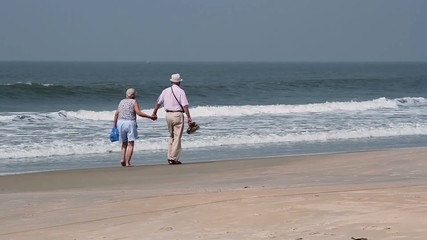 Old couple walk on the beach