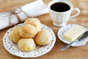 Brazilian snack pao de queijo (cheese bread) white plate butter