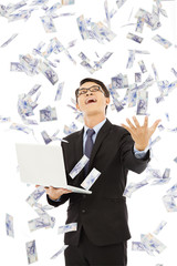 happy business man holding a laptop and  catching money