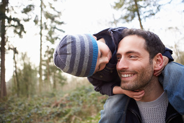 Father Carrying Son On Shoulders During Countryside Walk