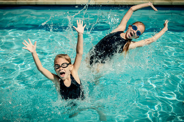 two happy little girls playing  in the swimming pool