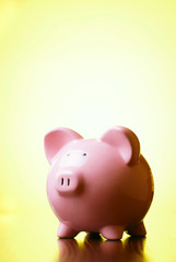 Pink piggy bank on a bright yellow background