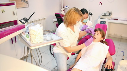 dentist nurse and little girl in dental office