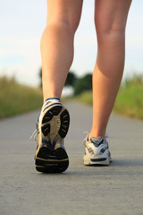 A pair of athlaetic, female legs running in the countryside.