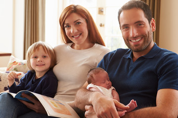 Family Sitting On Sofa With Newborn Baby