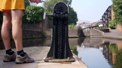 Using a windlass to open a canal lock paddle.