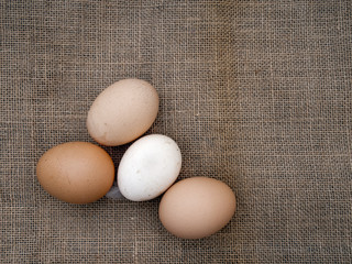 Farm fresh eggs assorted colours, on hessian old rustic fabric