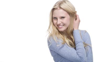 Junge blonde Frau lächelt vor weissem Hintergrund