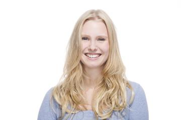 Junge blonde Frau lächelt gegen weisser Hintergrund