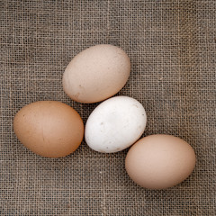 Real fresh farm eggs on old hessian, burlap background cloth.