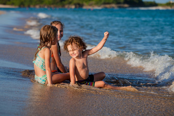 three happy kids playing on beach at the day time