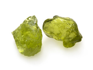 Green peridot raw gemstones on the white background.
