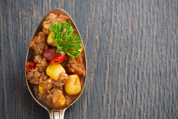Mexican dish chili con carne in a spoon on wooden background
