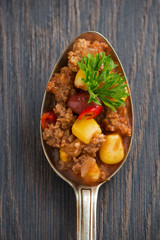 spicy Mexican dish chili con carne in a spoon, conceptual photo