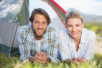Attractive couple smiling at camera from inside their tent