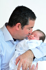 Father and newborn baby kissing and hugging.