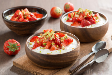 yogurt with fresh strawberries and pistachios in a wooden bowls