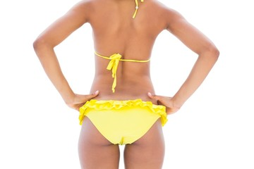 Fit girl in yellow bikini mid section rear view