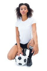 Pretty football player in white holding ball looking at camera