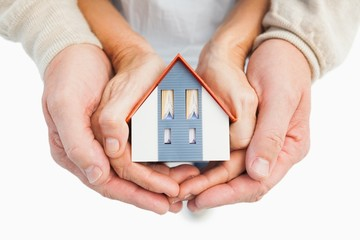 Couple holding small model house in hands