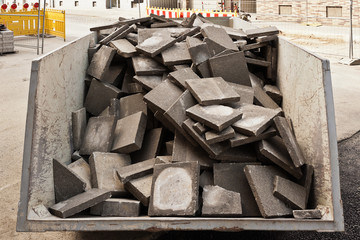 Entsorgung alter Gehwegplatten aus Beton in einem Container