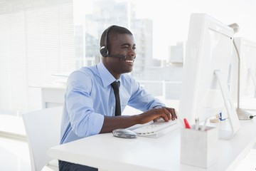 Happy businessman working at his desk wearing headset