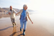 Senior Couple Running Along Winter Beach - 67943429