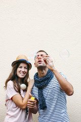Beautiful young couple blowing soap bubbles.