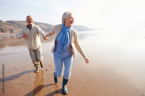 Leinwandbild Motiv Senior Couple Running Along Winter Beach