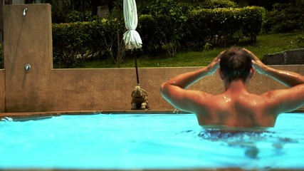 Tanned Muscular Man Relaxing in Pool. Slow Motion.