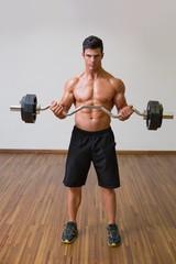 Shirtless muscular man lifting barbell in gym