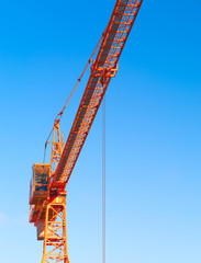 Hoisting crane. Fragment against the blue sky.