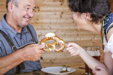 Man and woman with pretzel, beer and white sausage
