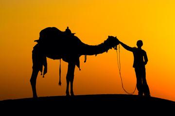 Silhouette man and camel at sunset in desert, Jaisalmer, India