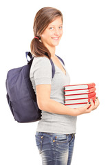 Teenage schoolgirl holding a stack of books