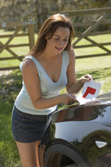Woman holding a L leaner driver plate by a car