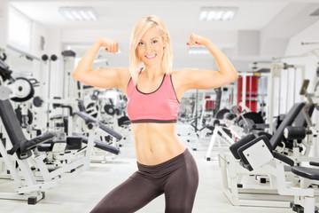 Female bodybuilder showing her biceps in a gym