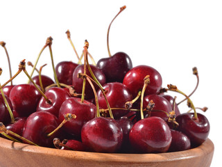 Red cherries in a wooden bowl on a white