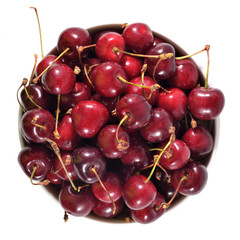 Top view of red cherries in a white bowl on a white
