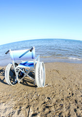 wheelchairs for disabled people with steel wheels on the beach